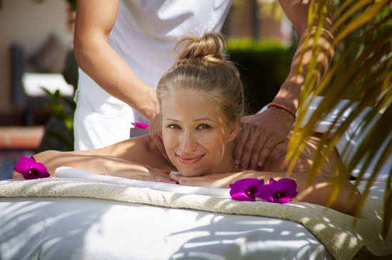 Young beautiful blonde caucasian woman gets massage and beauty treatment in luxury resort. Horizontal shape, front view
